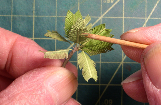 Al paints tiny palm fronds for his sculpture Lava Island